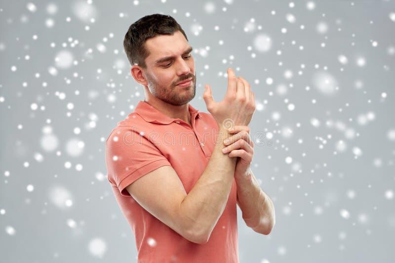 Olyckligt manlidande från smärtar i hand över snö arkivfoton