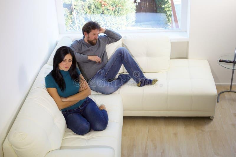 Olyckligt parsammanträde på soffan som är ilsken efter kamp royaltyfri foto