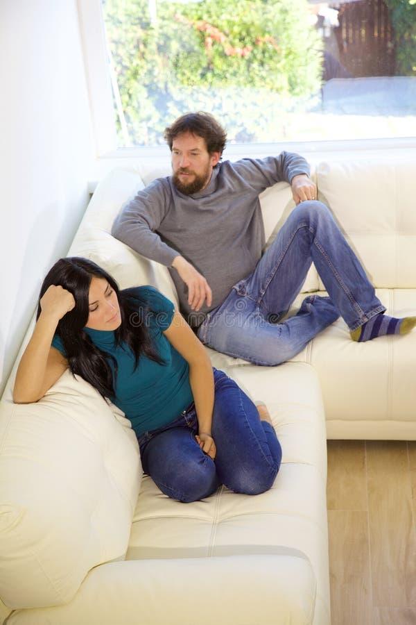Olyckligt parsammanträde på soffan som är ilsken efter kamplodlinje fotografering för bildbyråer