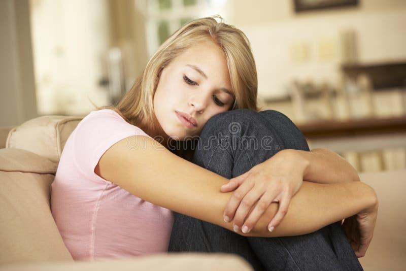 Olyckligt sammanträde för tonårs- flicka på Sofa At Home arkivfoto