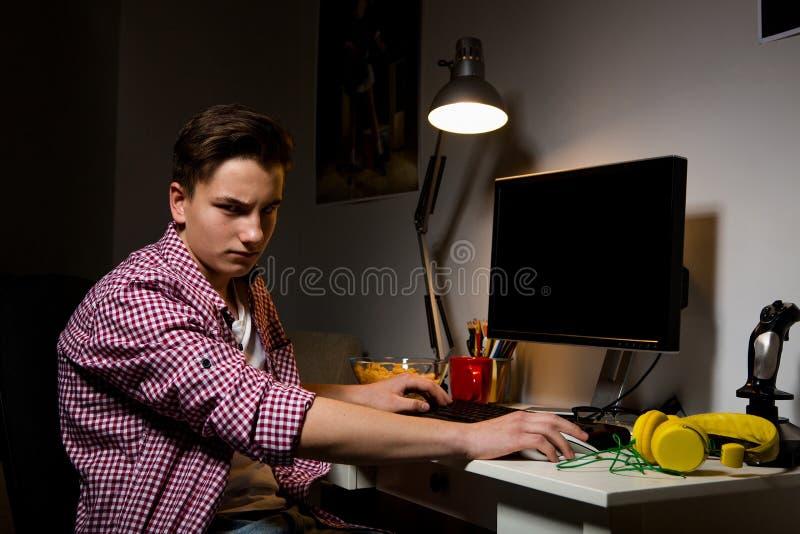 Olyckligt sammanträde för tonårs- pojke på datortabellen royaltyfri bild