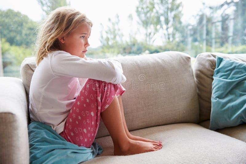Olyckligt ung flickasammanträde på Sofa At Home arkivfoton