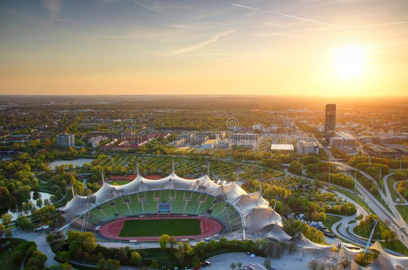 Aerial view of Olympic park with stadium at sunset in Munich. Olympiapark Munchen aerial view with Olympic stadium, skyscraper, highway junction and tower blocks royalty free stock photography