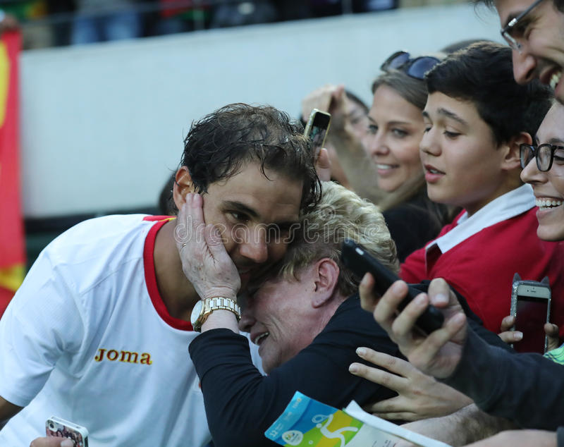 Olympic champion Rafael Nadal of Spain with tennis fan after men`s singles semifinal of the Rio 2016 Olympic Games. RIO DE JANEIRO, BRAZIL - AUGUST 12, 2016 stock photo