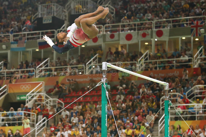 Olympic champion Simone Biles of United States competes on the uneven bars at women's team all-around gymnastics at Rio 2016. RIO DE JANEIRO, BRAZIL - AUGUST 9 stock photo