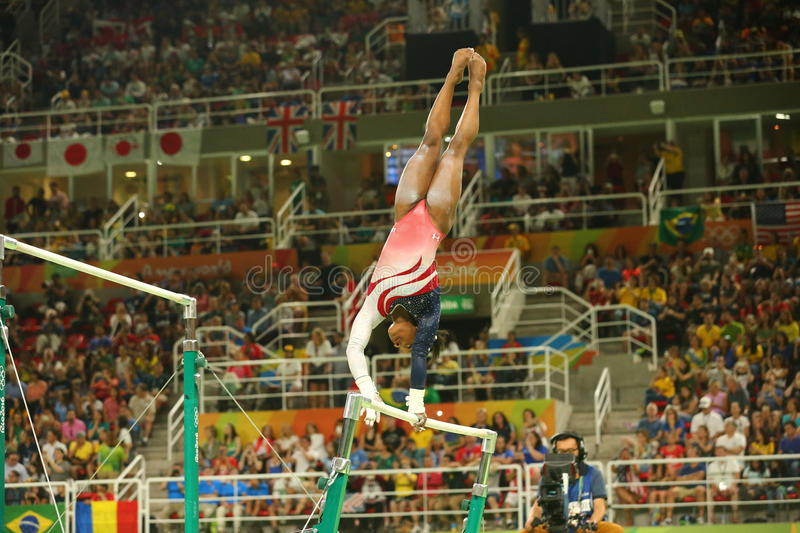 Olympic champion Simone Biles of United States competes on the uneven bars at women's team all-around gymnastics at Rio 2016. RIO DE JANEIRO, BRAZIL - AUGUST 9 stock images