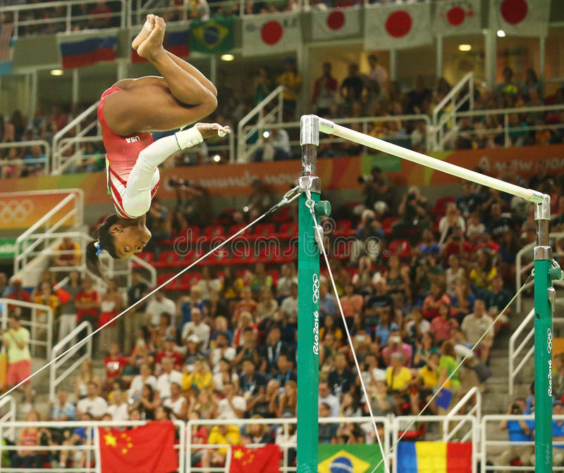 Olympic champion Simone Biles of United States competes on the uneven bars at women's team all-around gymnastics at Rio 2016. RIO DE JANEIRO, BRAZIL - AUGUST 9 stock photos
