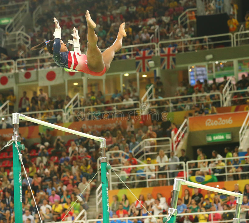 Olympic champion Simone Biles of United States competes on the uneven bars at women's team all-around gymnastics at Rio 2016. RIO DE JANEIRO, BRAZIL - AUGUST 9 royalty free stock photo