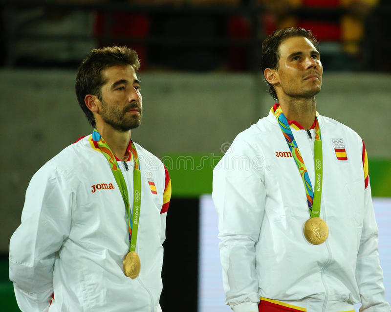 Olympic champions Mark Lopez and Rafael Nadal of Spain during medal ceremony after victory at men's doubles final. RIO DE JANEIRO, BRAZIL - AUGUST 12, 2016 royalty free stock photography