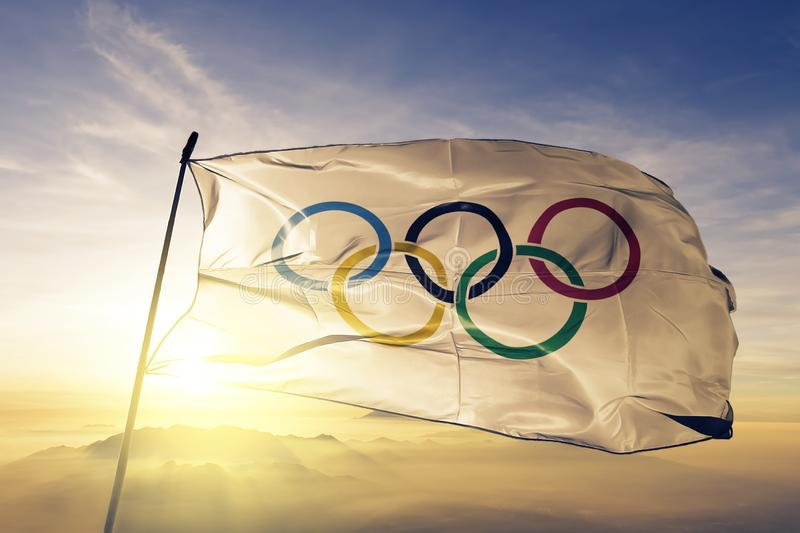 Olympic rings with transparent rims flag textile cloth fabric waving on the top sunrise mist fog. Beautiful royalty free illustration