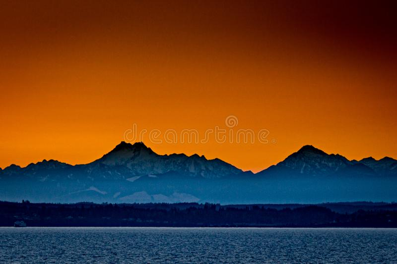 Sunset over mountains in Olympic National Park, Washington. Sunset with orange skies over mountains in Olympic National Park in Kingdton, Washington stock photography