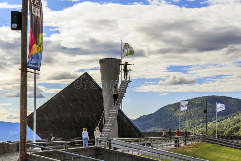 Olympic torch in Lillehammer, Norway. LILLEHAMMER, NORWAY - JULY 6, 2016: There are tourists near Olympic torch, that was built in 1993, specifically to the XVII stock photos