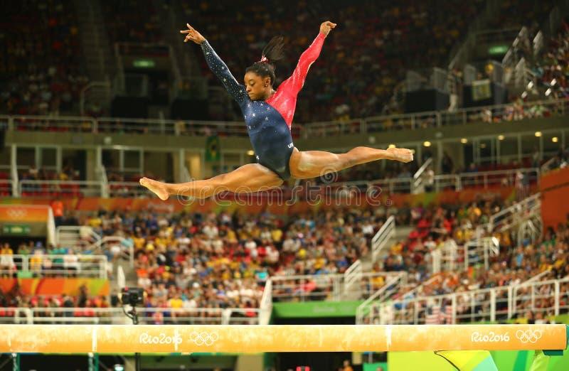 Olympische kampioen Simone Biles van Verenigde Staten die op de evenwichtsbalk bij globale de gymnastiekkwalificatie van vrouwen  stock afbeeldingen
