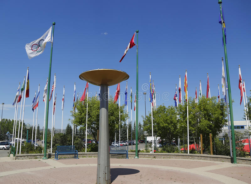 Olympischer großer Kessel und internationale Flaggen in Kanada-Olympiapark in Calgary lizenzfreies stockbild