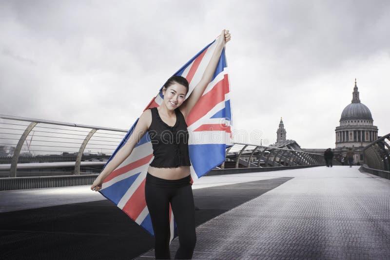 Olympischer Konkurrent mit Union Jack vor St Paul Kathedrale in London stockfotos