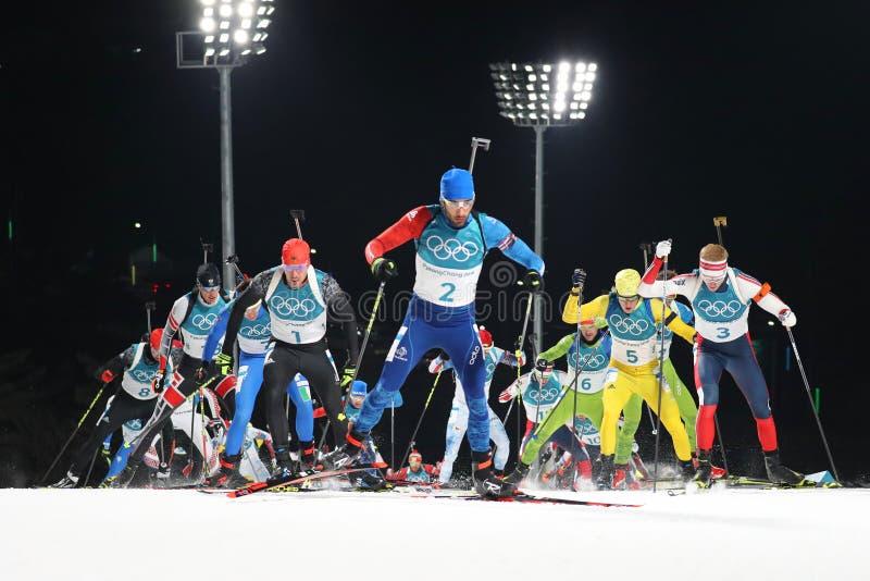Olympischer Meister Martin Fourcade von Frankreich konkurriert im Biathlonmänner ` s 15km Massenanfang an den 2018 Winter Olympic lizenzfreie stockbilder
