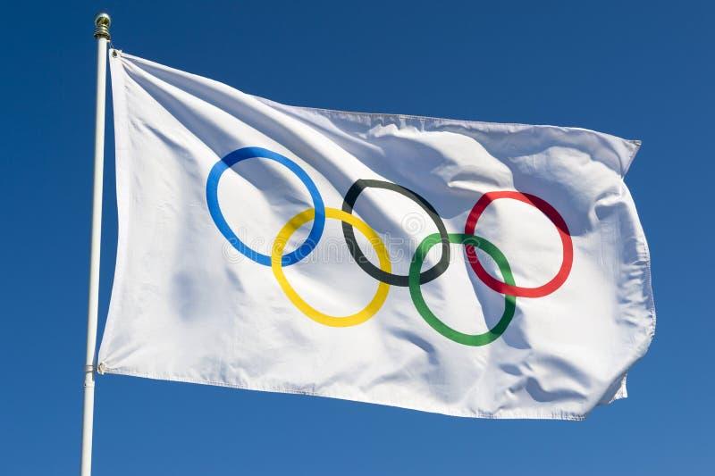 Olympisk flagga som fladdrar i ljus blå himmel arkivfoto