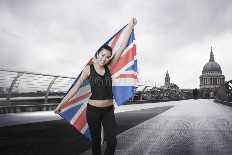 Olympisk konkurrent med Union Jack som är främst av Sts Paul domkyrka i London arkivfoton