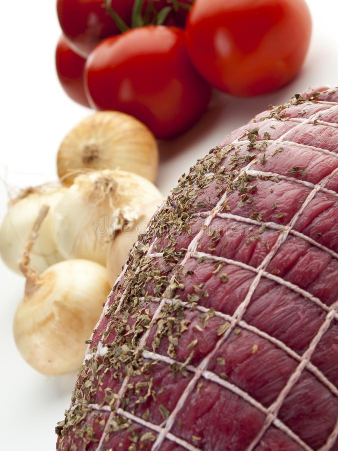 Round meat tied for roasting with onions and tomatoes 4 royalty free stock image