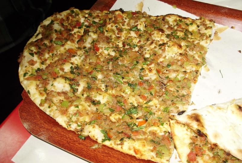 Pide is a national Turkish dish. Something between a pizza and a pie. The pide shape resembles a boat with minced meat, but the filling is very juicy due to stock photography
