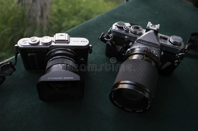 An Olympus Pen E-PL8 and An Olympus OM-1. Istanbul, Turkey - May 1, 2018 : An Olympus Pen E-PL8 and An Olympus OM-1 are on a table. Pen E-PL8 is a digital royalty free stock photo
