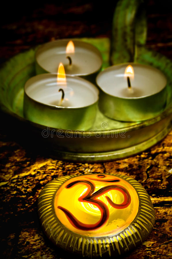 Om. Stone with the symbol om or aum with three candles like a concept for spiritual oriental philosophy, healing energy of reiky and chakra