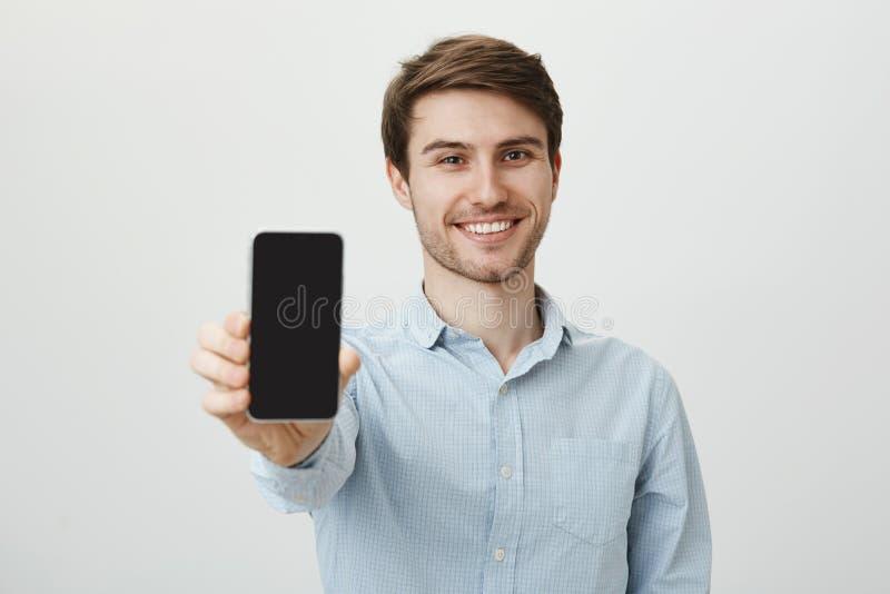 Om du söker den nya telefonen, köp denna modell Stående av den gladlynta attraktiva vita mannen med borstet som drar handen in mo royaltyfria foton