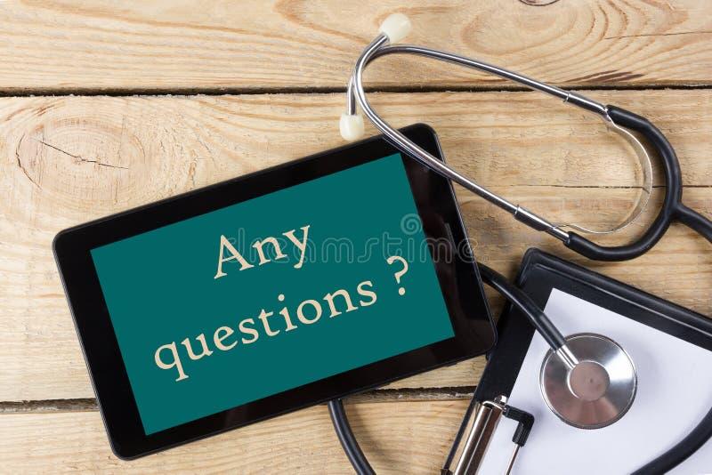 Om het even welke vragen? - Werkplaats van een arts Tablet, stethoscoop, klembord op houten bureauachtergrond Hoogste mening stock afbeelding