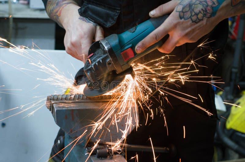 Om metaal te snijden met een malende machine met vonken stock fotografie