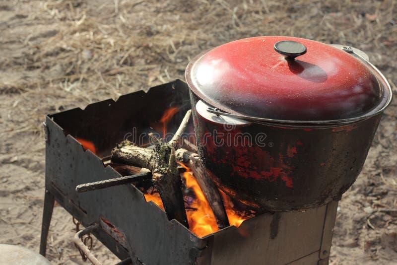Om op een brand in een bowlingspelerhoed te koken stock afbeeldingen