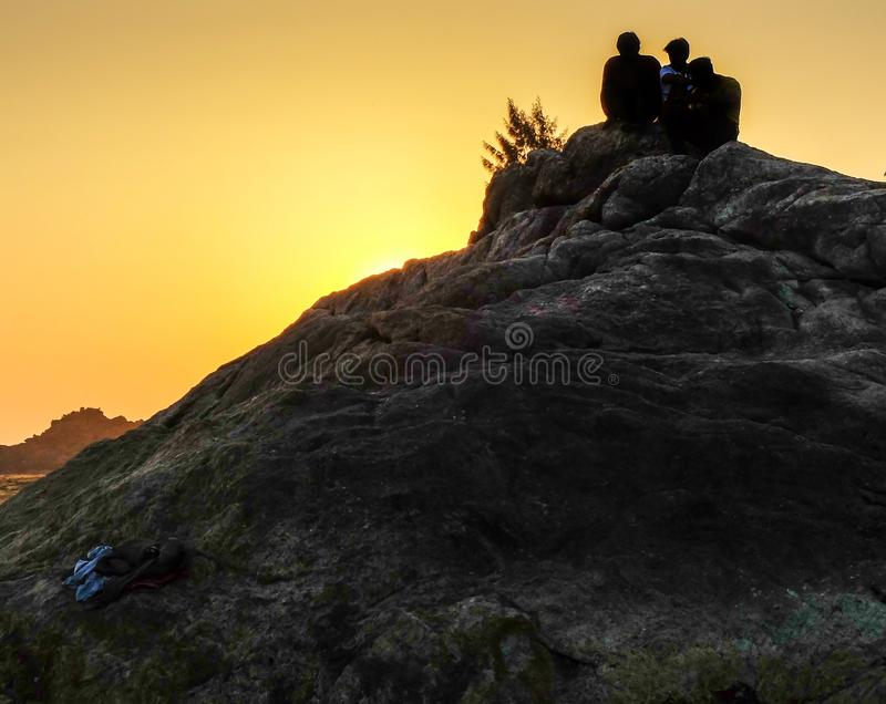 OM-STRAND, GOKARNA, KARNATAKA/INDIA-FEBUARY 2, 2018: De jonge mensen zitten op een heuvel van rotsen, lettend op de zonsondergang royalty-vrije stock foto
