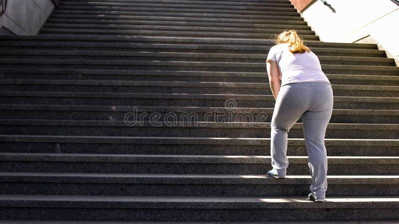 Om treden voor zwaarlijvig meisje, overwinning over moeheid hard te beklimmen voor doel het bereiken royalty-vrije stock afbeeldingen