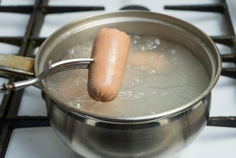 Om uit een pot van kokend water gekookte worsten te krijgen De hete worst is op de vork Het koken thuis op het gasfornuis royalty-vrije stock afbeelding