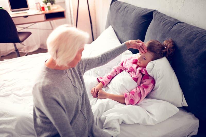 Oma die aan haar meisje komen die in bed liggen die ziek voelen stock foto