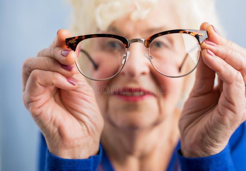 Oma die door glazen kijken stock afbeeldingen