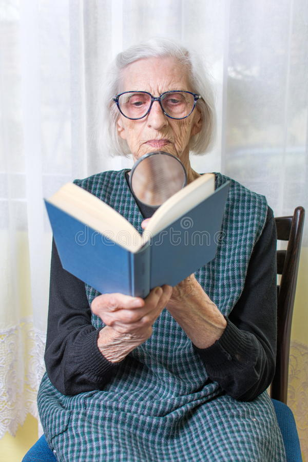 Oma die een boek leest door vergrootglas royalty-vrije stock afbeeldingen
