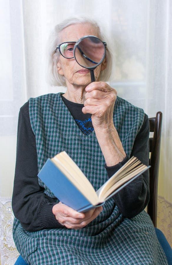 Oma die een boek leest door vergrootglas stock foto