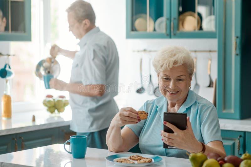 Oma die een celtelefoon met behulp van royalty-vrije stock afbeelding