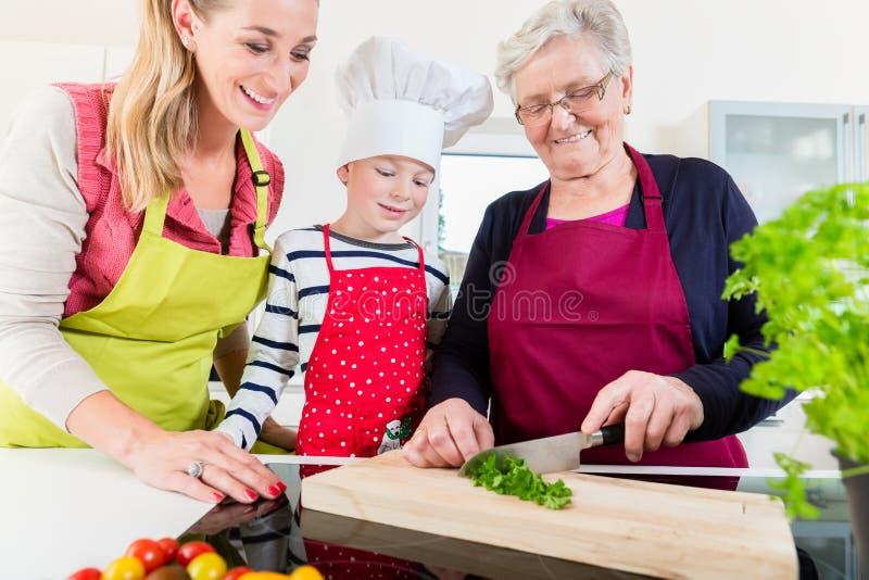 Oma die oud familierecept tonen aan kleinzoon en dochter stock afbeeldingen