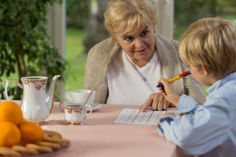 Oma die zijn kleinzoon helpt royalty-vrije stock foto's