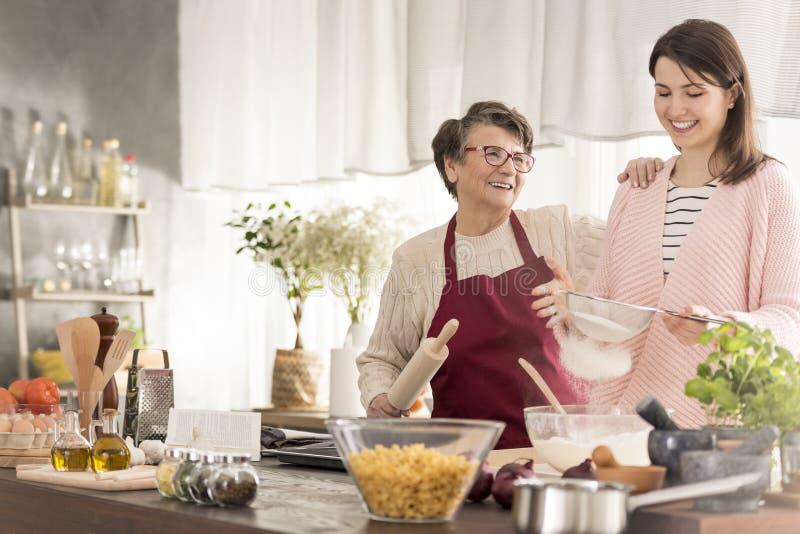 Oma en kleindochter die een cake bakken stock afbeelding