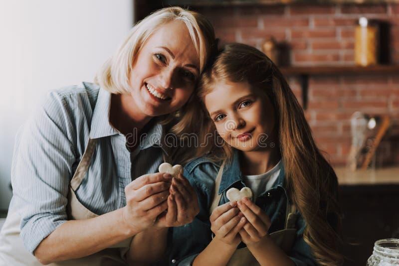 Oma en Kleindochterbakselkeuken thuis stock fotografie