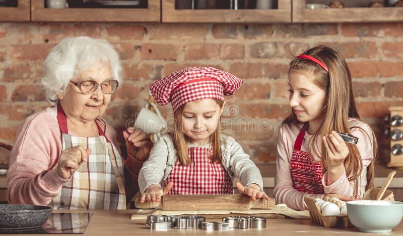 Oma en kleindochters die deeg uitspreiden royalty-vrije stock fotografie