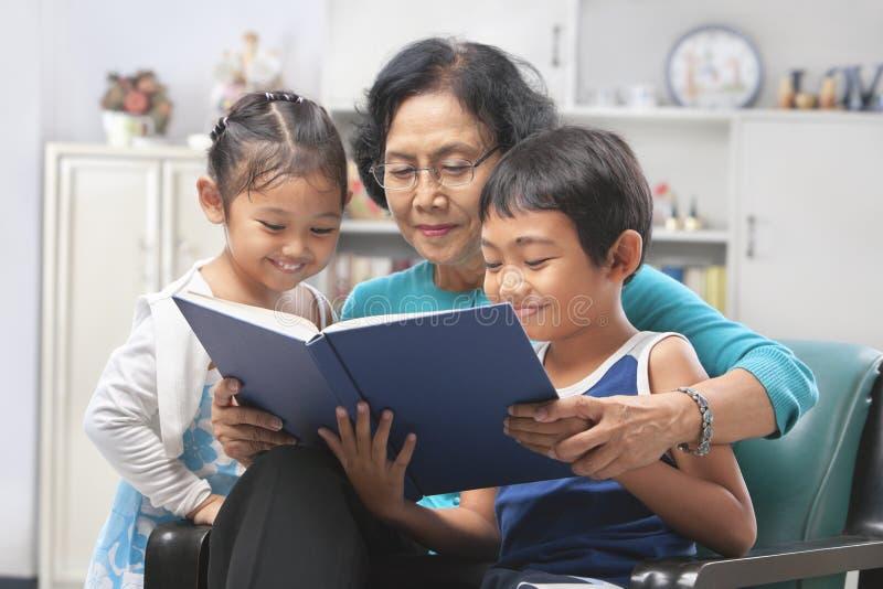 Oma en kleinkinderen die boek samen lezen stock foto's