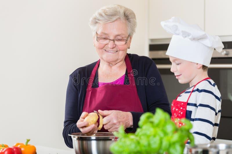 Oma en kleinzoon die samen koken stock afbeelding