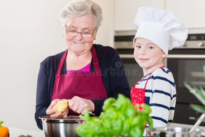 Oma en kleinzoon die samen koken stock afbeeldingen
