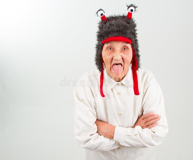 Oma in grappige hoed die haar tong tonen royalty-vrije stock afbeelding