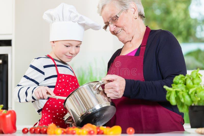 Oma het koken samen met haar kleinzoon stock fotografie