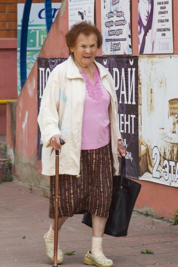 Oma mit einem Stock stockfotografie