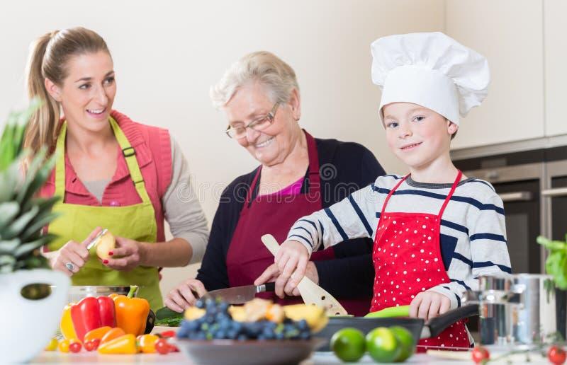Oma, mum en zoon die terwijl het koken in keuken spreken royalty-vrije stock afbeelding